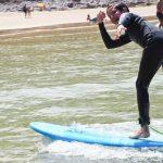 Saludo surfero de pie en la ola